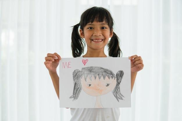 Criança pequena e fofa em idade pré-escolar se desenhando em casa