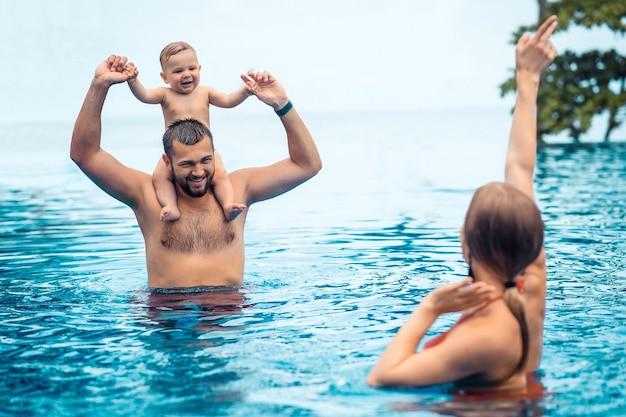 Criança pequena e pais se divertindo na piscina