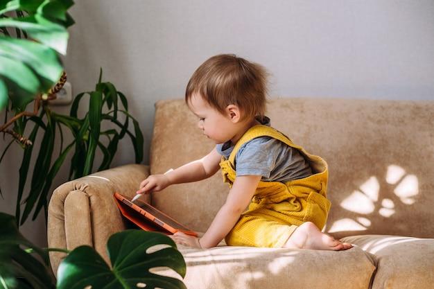 Criança pequena em casa no sofá com um tablet e uma caneta stylus desenhando