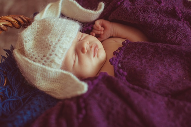 Criança pequena em chapéu como orelhas de coelho dorme sob o cachecol