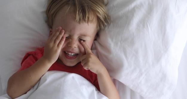 Criança pequena encontra-se na cama e esfrega os olhos. um menino bonito encontra-se na roupa pastel branca e sorri. vista superior da criança feliz e alegre