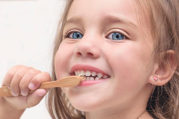 Criança pequena escova os dentes com uma escova de dentes de bambu