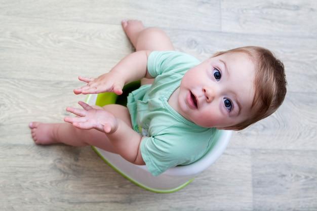 Criança pequena está sentada no penico. ensinando o bebê ao penico. conceito de cuidados com o bebê