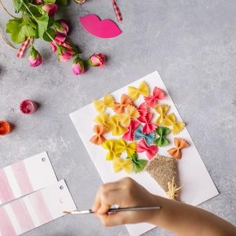 Criança pequena fazendo um buquê de flores de papel colorido e massas coloridas.