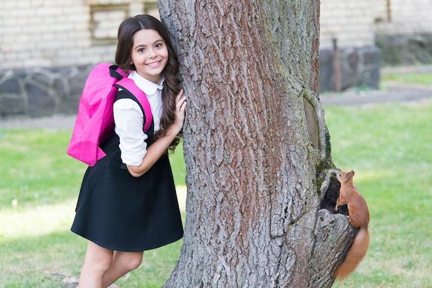 Criança pequena feliz de uniforme com esquilo de pesquisa mochila escolar subindo em árvore no parque, zoologia.