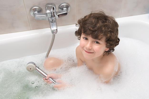 Criança pequena feliz e sorridente no banho