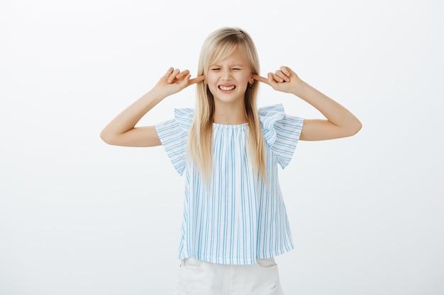 Criança pequena irritada descontente com cabelo loiro e blusa azul, cobrindo as orelhas com os dedos indicadores e fazendo careta, ouvindo um som irritante, de pé sobre uma parede cinza
