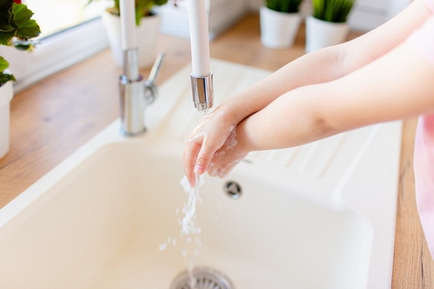 Criança pequena, lavar as mãos com água e sabão, close-up. o rosto não está visível.