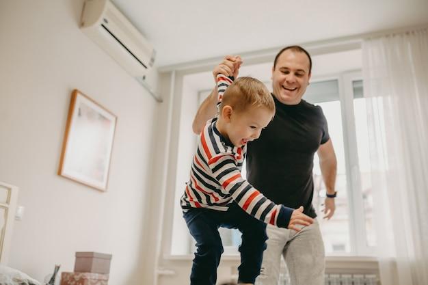 Criança pequena loira brincando e pulando junto com seu pai durante um dia de fim de semana