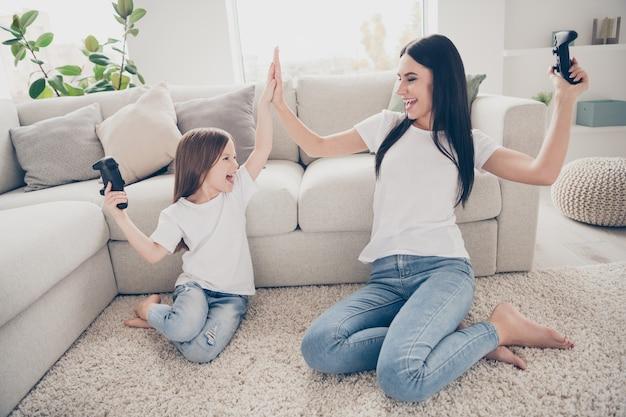 Criança pequena mamãe joga jogo de vitória bate palmas na sala