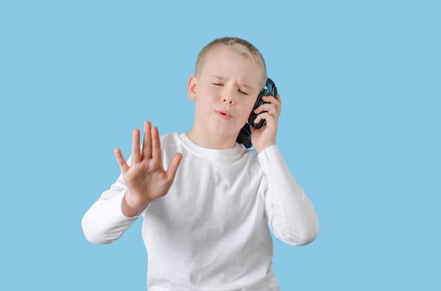 Criança pequena mantenha a mão nos fones de ouvido, gostando de ouvir música e cante