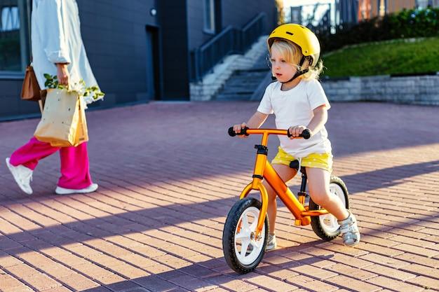 Criança pequena menina com capacete e bicicleta de equilíbrio brincando ao ar livre