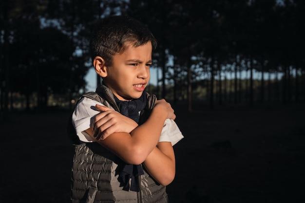 Criança pequena no frio com os braços cruzados ao ar livre.