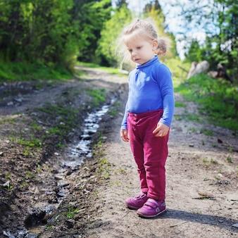 Criança pequena olha para o riacho na floresta.