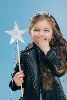 Criança pequena positiva superemotiva cobre a boca com uma palma, veste jaqueta de couro preta elegante e coroa