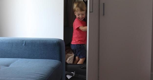 Criança pequena que joga em casa um jogo de viajante garoto em uma mala de viagem