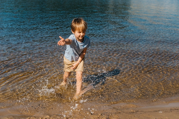 Criança pequena, salpicos de água na praia