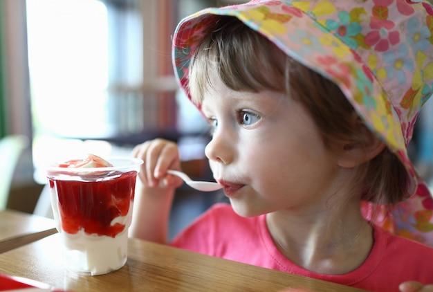 Criança pequena satisfeita lambe a colher com gelo