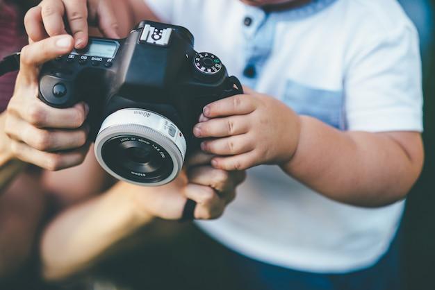 Criança pequena, segurando uma câmera
