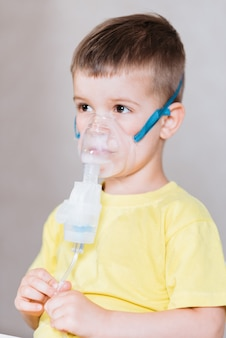 Criança pequena trata o inalador de bronquite em casa