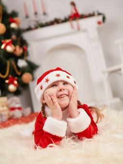 Criança pequena vestida como papai noel com mãos na face
