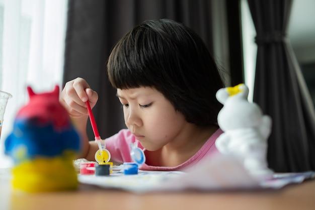 Criança pinta a cor no conceito de educação de papel