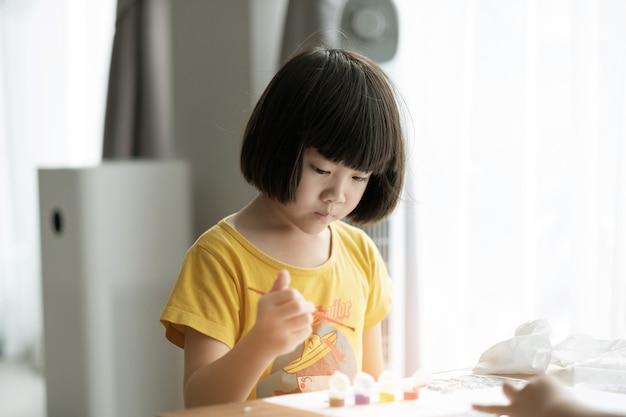 Criança pinta a cor no papel, conceito de educação