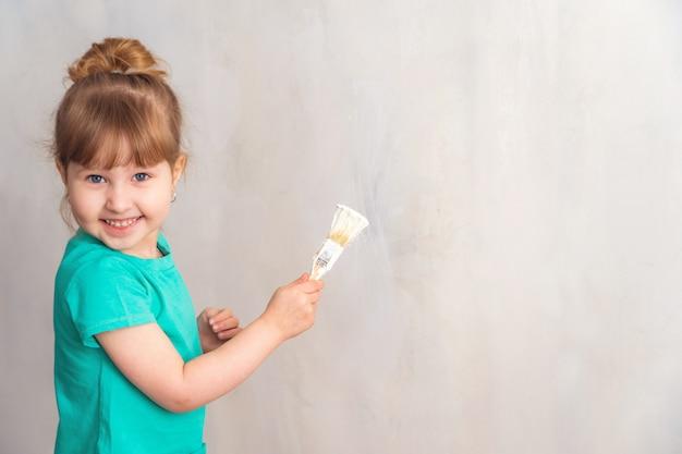 Criança pinta a parede com um pincel de tinta branca