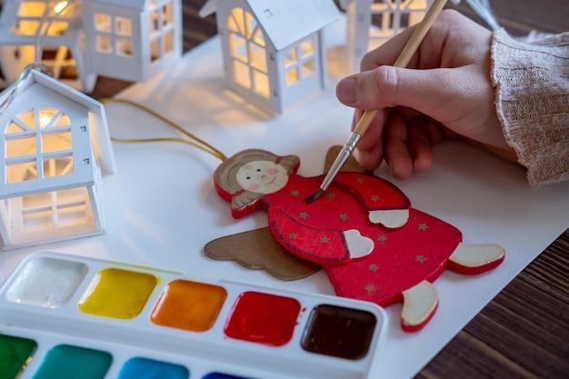 Criança pinta brinquedos, decorações para a árvore de natal, criatividade infantil, conceito