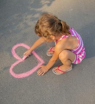 Criança pinta giz no coração de asfalto. foco seletivo.
