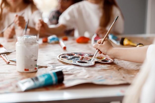 Criança pintando à mão em papel com dois colegas de classe ao fundo