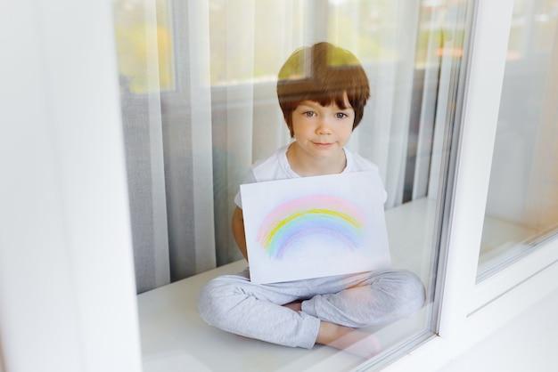 Criança pintando arco-íris durante quarentena de covid-19 em casa