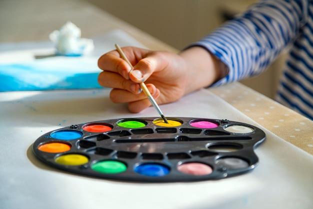 Criança pintando com tinta aquarela na escola em casa.