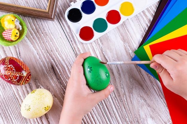 Criança pintando ovos de páscoa. dia de páscoa