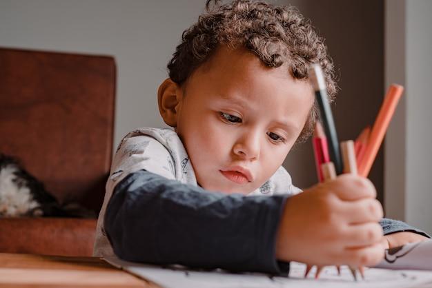 Criança pintando seu livro de desenho com muitas cores. descobrindo talentos artísticos em uma pandemia