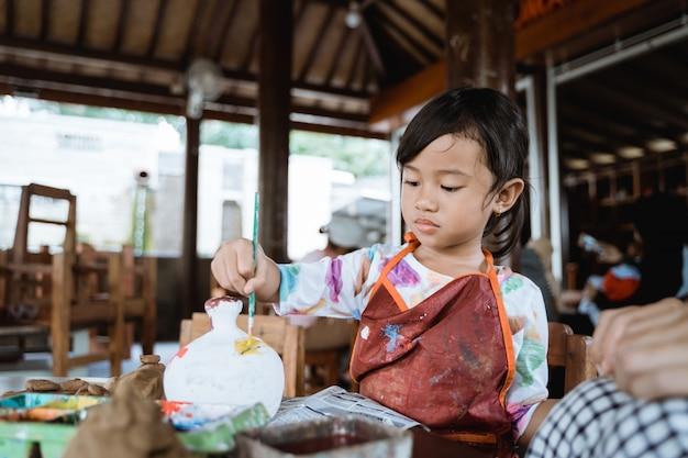 Criança pintando vaso de cerâmica com pincel