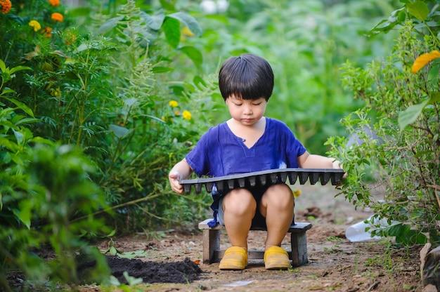 Criança plantando vegetais em uma bandeja conceito de atividade de aprendizagem infantil em casa