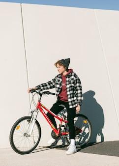 Criança posando com sua bicicleta ao ar livre