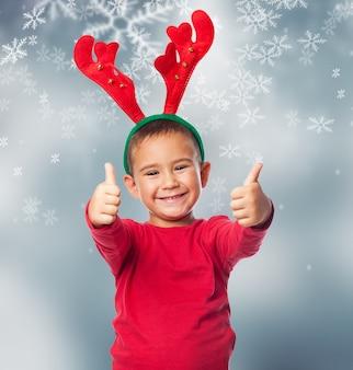 Criança positiva com chifres de rena e mostra os polegares acima
