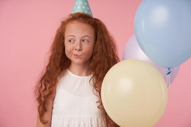 Criança positiva do sexo feminino com cabelo ruivo cacheado em roupas festivas e boné de aniversário fica contra um fundo rosa, sorri com alegria e olhando de lado para os balões colore. crianças e conceito de celebração