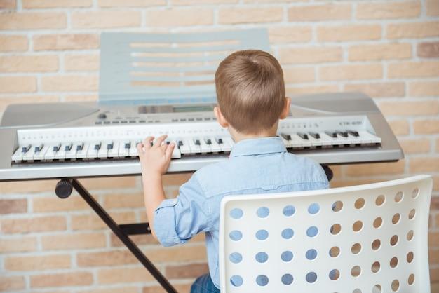 Criança praticando piano elétrico durante uma sessão de música na academia