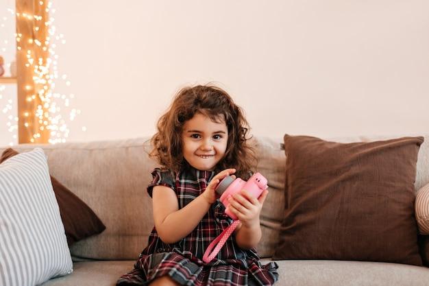 Criança pré-adolescente sorridente segurando a câmera. tiro interno de criança encaracolada sentada no sofá.