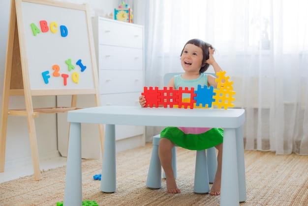 Criança pré-escolar 3 anos brincando com blocos de brinquedo colorido.