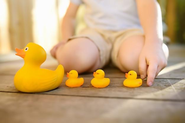 Criança pré-escolar aprende a contar com patinhos de brinquedo