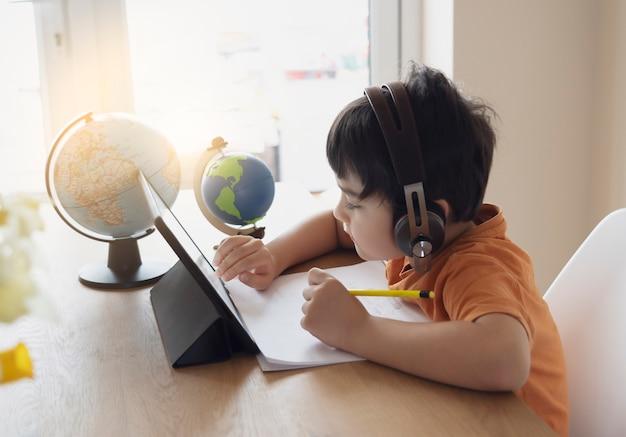 Criança pré-escolar usando tablet e usando fones de ouvido