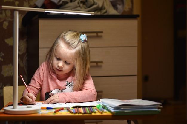 Criança preschooler aprende a desenhar e escrever em cadernos em casa