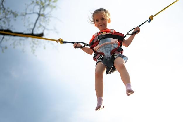 Criança pulando elástico de trampolim infantil parque de diversões menina pulando na atração