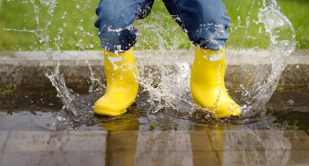 Criança pulando na piscina de água no verão ou no dia de outono