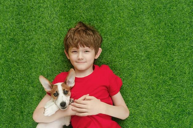Criança que abraça o jaque russell do cachorrinho e que encontra-se no tapete verde.
