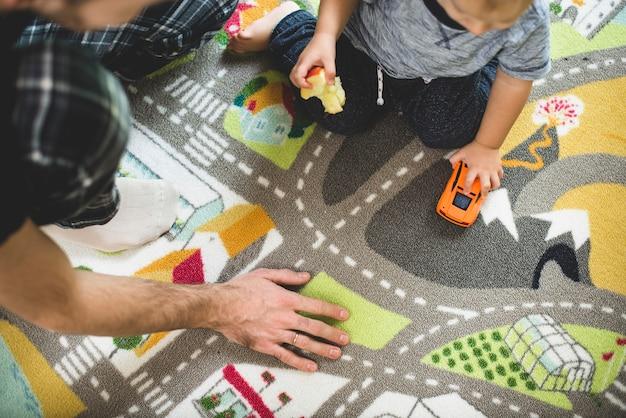 Criança que come uma maçã e jogando com um carro de brinquedo